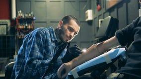 Artista masculino em processo de fazer uma tatuagem em seu salão de beleza filme