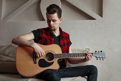 Artista masculino novo que joga a guitarra imagem de stock