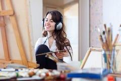 Artista na imagem das pinturas dos fones de ouvido na lona imagem de stock