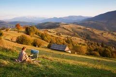 Artista novo que pinta uma paisagem Fotos de Stock
