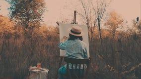 Artista novo que pinta uma paisagem do outono A menina na natureza do artista tira video estoque