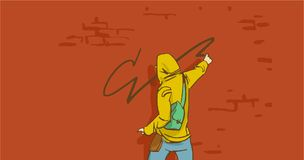 Artista Person In Hoodie Painting On de la calle de la historieta una pared de ladrillo Foto de archivo libre de regalías