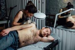 Artista profesional del tatuaje de la muchacha morena joven el amo dibuja en el brazo del hombro del ` s del hombre Foto de archivo libre de regalías