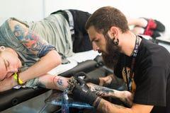Artista profesional que hace el tatuaje en el brazo del cliente Fotos de archivo libres de regalías