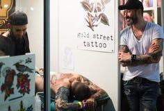 Artista profesional que hace el tatuaje en el cliente masculino detrás Imagen de archivo