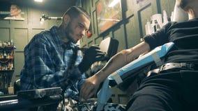 Artista professionista che tatua una persona con il braccio artificiale archivi video