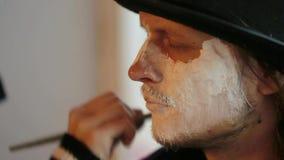 Artista que aplica maquillaje sobre cara del ` s del hombre en Halloween almacen de video