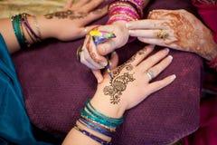 Artista que aplica o projeto do Henna do pavão às mãos de um Womanâs Imagens de Stock