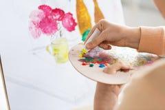 Artista que aplica a pintura à paleta no estúdio da arte Foto de Stock