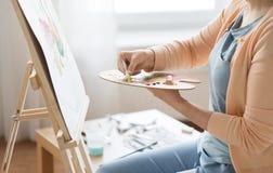 Artista que aplica a pintura à paleta no estúdio da arte Imagens de Stock Royalty Free