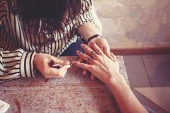 Artista que aplica a tatuagem da hena nas mãos das mulheres Fotografia de Stock