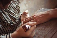 Artista que aplica a tatuagem da hena nas mãos das mulheres Imagens de Stock Royalty Free