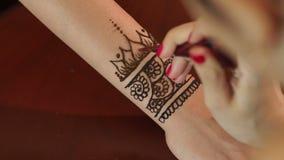Artista que aplica a tatuagem da hena nas mãos do ` s da noiva vídeos de arquivo