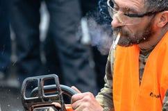 Artista que cinzela a madeira com a serra de cadeia durante euromaidan em Ucrânia Fotografia de Stock Royalty Free