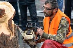 Artista que cinzela a madeira com a serra de cadeia durante euromaidan em Ucrânia Foto de Stock