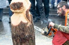 Artista que cinzela a madeira com a serra de cadeia durante euromaidan em Ucrânia Imagens de Stock