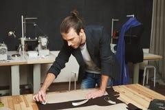 Artista que cria a obra-prima Feche acima do desenhista de roupa masculino bonito novo com penteado na moda e elegante foto de stock