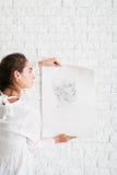 Artista que cuelga su retrato del lápiz en la pared fotografía de archivo libre de regalías