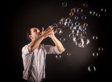 Artista que sopla muchas burbujas de jabón de sus manos Foto de archivo libre de regalías