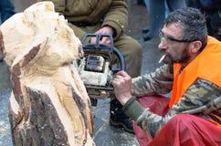 Artista que talla la madera con la motosierra durante euromaidan en Ucrania Fotos de archivo libres de regalías