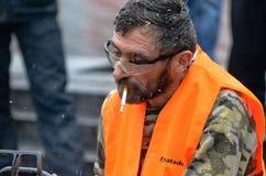 Artista que talla la madera con la motosierra durante euromaidan en Ucrania Fotos de archivo