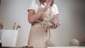 Artista que trabalha com partes grandes da argila em uma oficina filme