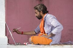 Artista que trabalha na pintura nos ghats do Ganges River em Varanasi, Índia Fotografia de Stock