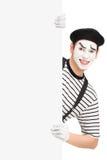 Artista sorridente del mimo che posa dietro un pannello in bianco fotografie stock