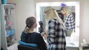 Artista y modelo de maquillaje Blonde joven Las cejas del dibujo del artista de maquillaje a una muchacha bonita con un cepillo p metrajes