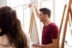 Artistas com as armações que pintam na escola de arte Fotos de Stock