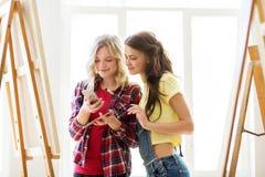 Artistas con smartphone en el estudio o la escuela del arte Foto de archivo