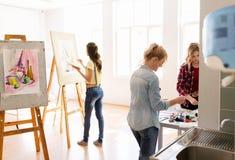 Artistas da mulher com as cores que pintam na escola de arte Imagens de Stock Royalty Free