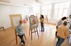 Artistas da mulher com as escovas que pintam na escola de arte Fotografia de Stock Royalty Free