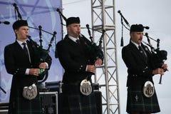 Artistas del funcionamiento, orquesta,  tubos nacionales escoceses y tambores de los instrumentos musicales del conjunto Fotos de archivo