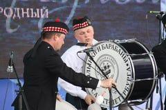Artistas del funcionamiento, orquesta,  tubos nacionales escoceses y tambores de los instrumentos musicales del conjunto Imagenes de archivo