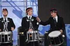 Artistas del funcionamiento, orquesta,  tubos nacionales escoceses y tambores de los instrumentos musicales del conjunto Foto de archivo libre de regalías