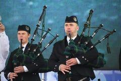 Artistas del funcionamiento, orquesta,  tubos nacionales escoceses y tambores de los instrumentos musicales del conjunto Imagen de archivo