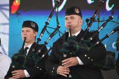 Artistas del funcionamiento, orquesta,  tubos nacionales escoceses y tambores de los instrumentos musicales del conjunto Foto de archivo