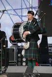 Artistas del funcionamiento, orquesta,  tubos nacionales escoceses y tambores de los instrumentos musicales del conjunto Imagen de archivo libre de regalías