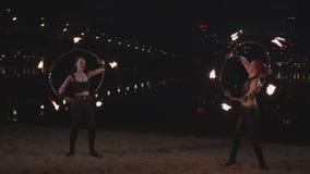 Artistas expertos que tuercen aros del hula del fuego por las manos almacen de video