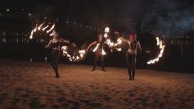 Artistas jovenes del fireshow que hacen juegos malabares la llama cerca del río metrajes
