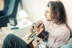 Artiste aux cheveux longs émotif étant concentré sur l'instrument de musique personnel images libres de droits