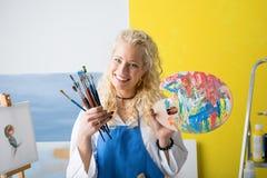 Artiste avec des pinceaux et palette de couleurs dans des ses mains Images stock