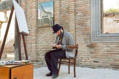 Artiste barbu, semblable à Niko Pirosmani populaire, peintures de dessin au chevalet pendant le week-end Image libre de droits