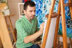 Artiste bel travaillant à une peinture photo stock