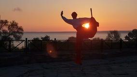 Artiste dans la danse folklorique ukrainienne de costume sur des échasses sur la plage de mer au coucher du soleil dans le ralent banque de vidéos