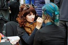 Artiste dans le style de steampunk créant le maquillage pour la jeune femme au ` lumineux de personnes de ` de festival le jour d Photo stock