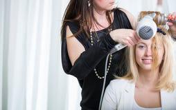 Artiste de coiffeur/coiffure travaillant aux cheveux d'une jeune femme Photo stock