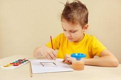 Artiste de débutant dans des couleurs jaunes de peinture de chemise Image stock
