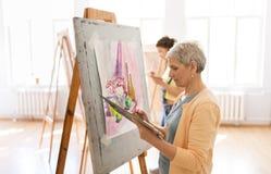 Artiste de femme avec la peinture de chevalet à l'école d'art Image stock
